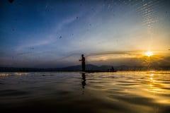 Kasta fiske på solnedgången Royaltyfri Bild