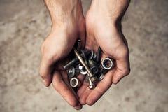Kasta i sig rostiga hjälpmedel för järn, och skruvar mans in händer Fotografering för Bildbyråer