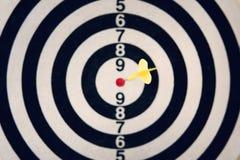 Kasta sig pilen som slår målet av darttavlan på vit bakgrund Slå bullseyen Klart syfte Brunn-siktat kasta för pil Mor royaltyfri fotografi