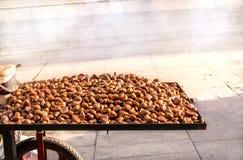 Kastanien für das Braten auf einem Warenkorb Stockfotografie