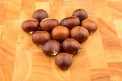 Kastanjer för säsongsbetonad frukt för höst bildade spanska på en träplatta Royaltyfri Bild
