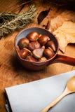 Kastanjer och mandlar i en kastrull över en wood tabell Royaltyfri Fotografi