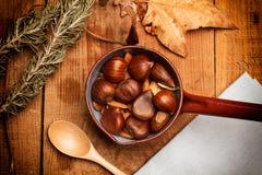 Kastanjer och mandlar i en kastrull över en wood tabell Fotografering för Bildbyråer