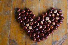 Kastanjer som bildar en hjärta på en träbakgrund Royaltyfri Foto