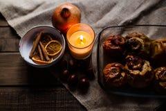 Kastanjer, stearinljus, kanel och apelsin i en bunke arkivfoto