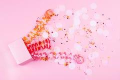 Kasten auf rosa Hintergrund mit mehrfarbigem serpantine und Konfettis lizenzfreie stockbilder