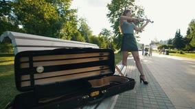 Kasten für die Violine, die auf der Bank vor Frau liegt, die eine Geige bei Sonnenuntergang spielt stock video