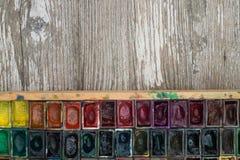 Kasten mit Aquarellen und Bürsten auf einer Holzoberfläche Stockfotografie