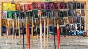 Kasten mit Aquarellen und Bürsten auf einer Holzoberfläche Stockbild