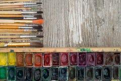 Kasten mit Aquarellen und Bürsten auf einer Holzoberfläche Lizenzfreies Stockfoto