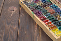 Kasten mit Aquarellen und Bürsten auf einer Holzoberfläche Stockfoto