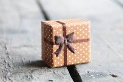 Kasten mit einem Geschenk auf einem Holztisch Stockfotografie