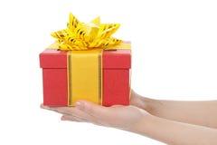 Kasten mit einem Geschenk in den Händen der Frauen Lizenzfreie Stockbilder
