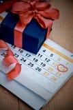 Kasten mit einem Geschenk gegen einen Kalender Stockbilder