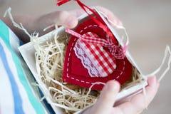 Kasten mit einem Geschenkvalentinsgrußherzen ein child& x27; s-Hand auf Valentine& x27; s stockfotos