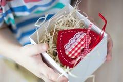 Kasten mit einem Geschenkvalentinsgrußherzen ein child& x27; s-Hand auf Valentine& x27; s stockbilder