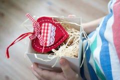 Kasten mit einem Geschenkvalentinsgrußherzen in einem child& x27; s-Hand auf Valentine& x27; s stockfotografie