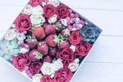 Kasten mit Erdbeeren und Rosen auf einem hellen hölzernen Hintergrund Lizenzfreie Stockfotografie