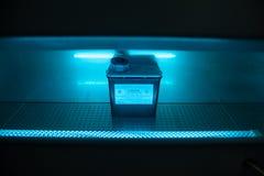 Kasten mit Gefahrenvirusinhalt unter UVuV-Licht Stockfotos