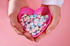 Kasten mit geformten Süßigkeiten des Herzens in den Händen stockbild