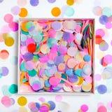 Kasten mit Konfettis auf buntem Hintergrund lizenzfreie stockbilder