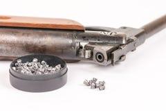 Kasten mit Metallluftgewehrkugeln und Luftgewehr mit hölzernem kundak gunstock über weißem Hintergrund stockfotografie
