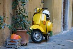 Kasten mit orange Kürbisen, Grünpflanze und gelbem Roller an der Wand des alten Hauses, Pienza, Italien Stockfotos