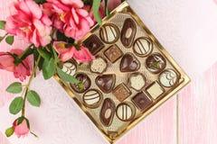 Kasten mit Schokoladen und rosa Blumen vorgewählt Stockbilder