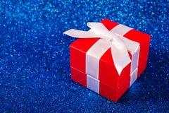Kasten mit Weihnachtsgeschenk auf glänzendem rotem Hintergrund Lizenzfreies Stockfoto