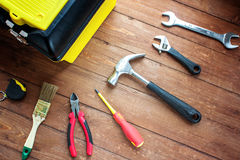 Kasten mit Werkzeugen und Werkzeugen auf einem hölzernen Hintergrund Lizenzfreie Stockfotos