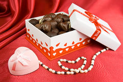 Kasten Schokoladen mit Geschenk und Perlen. Lizenzfreie Stockfotos