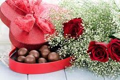 Kasten Schokoladen und Beauitful-Rosen Stockfotografie