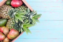 Kasten tropische Früchte im Kasten über blauer Tabelle Lizenzfreie Stockfotos