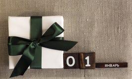 Kasten wird mit einem grünen Band, Geschenk, neues Jahr, am 1. Januar gebunden Lizenzfreies Stockfoto