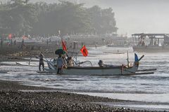 Bringing a fishing boat to shore in Kasumba, a traditional fishing village on Bali`s southern coast, Indonesia stock photos
