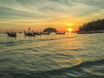 Kata beach sunset view. Kata beach, Phuket, sunset view with island, boats, cloudy sky, clouds, colors, turquoise water, aquamarine, green, red, yellow, orange royalty free stock images