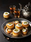 Kataifi, kadayif, kunafa, baklava pastry nest cookies with pistachios with tea. Cooking sweets turkish, or arabic traditional stock photo