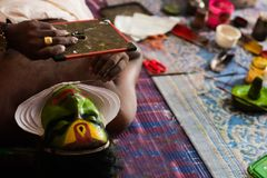 Katakhali dance performer doing face paint and makeup in front of hand held mirror.  stock image
