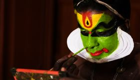 Katakhali dance performer doing face paint and makeup in front of hand held mirror.  stock images