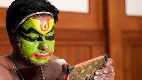 Katakhali dance performer doing face paint and makeup in front of hand held mirror.  stock photo