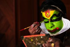 Katakhali dance performer doing face paint and makeup in front of hand held mirror.  royalty free stock image