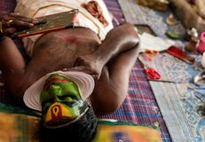 Katakhali dance performer doing face paint and makeup in front of hand held mirror.  stock photography