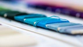 Katalog av trådar Mångfärgade möblemangtrådar Bakgrund för textilbransch med suddigt Makro begrepp av designen produktion arkivfoton