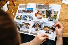 Katalog för fastighet för hus och för lägenheter för kvinnamedelläsning royaltyfri bild