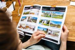 Katalog för fastighet för hus och för lägenheter för kvinnamedelläsning arkivbild