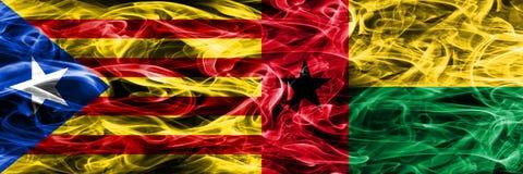 Katalonien gegen die Guinea-Bissau Kopien-Rauchflaggen nebeneinander gesetzt Dicke farbige seidige Rauchflaggen des katalanisches stock abbildung