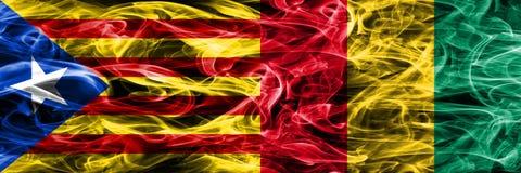 Katalonien gegen die Guinea-Kopienrauchflaggen nebeneinander gesetzt Dicke farbige seidige Rauchflaggen des katalanisches und des stock abbildung