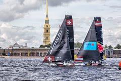 Katamaran för Red Bull seglinglag och Alinghi på extrema segla katamaran för seriehandling 5 springer i St Petersburg, Ryssland Arkivfoton