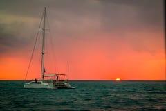 Katamaransegelbåt och solnedgång Arkivfoton