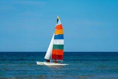 Katamaransegelbåten med ett mycket färgglat seglar arkivfoto